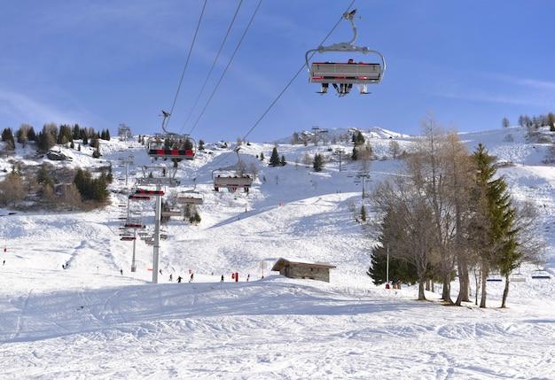 Teleférico sob o céu azul e acima da pista de esqui