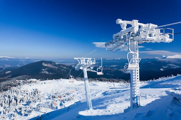 Teleférico vazio coberto de geada e neve com montanhas ao fundo