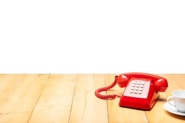 Telefone antigo vermelho e uma xícara de café