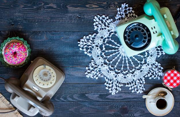 Telefone antigo vintage, com biscoitos, café, rosquinhas em uma mesa de madeira