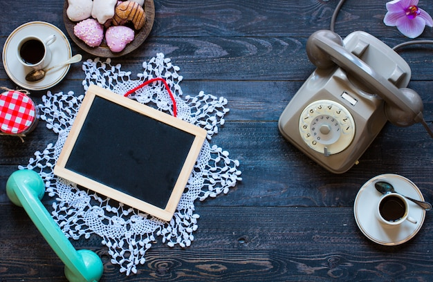 Telefone antigo vintage, com biscoitos, caffè, rosquinhas numa superfície de madeira,