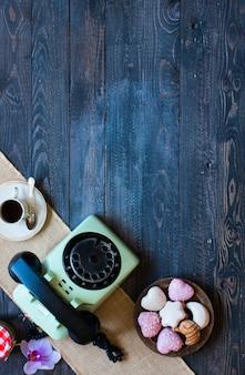 Telefone antigo vintage com donuts de café biscotti em um fundo de madeira