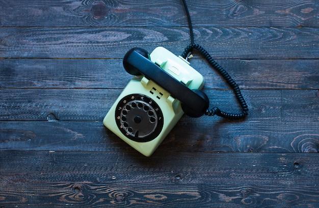 Telefone antigo vintage, em uma mesa de madeira