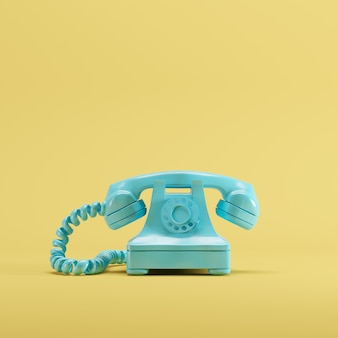 Telefone azul do vintage no fundo amarelo da cor pastel. conceito de ideia mínima.