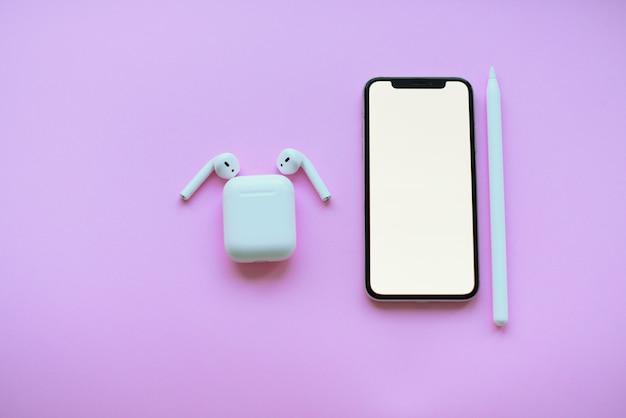 Telefone, cápsulas de ar e lápis em fundo rosa