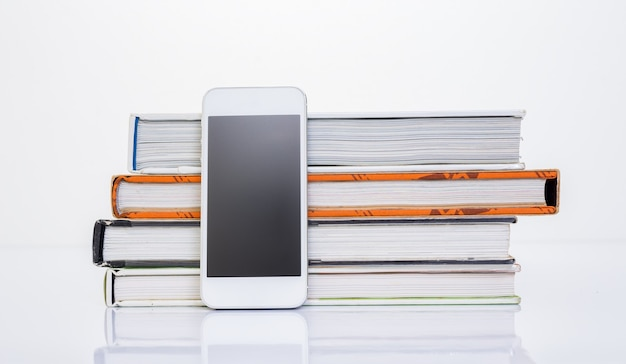 Telefone celular ao lado do grupo de livro em fundo branco