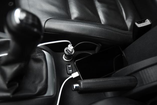 Telefone celular, bateria de carga do smartphone, carregamento no plugue do carro close-up