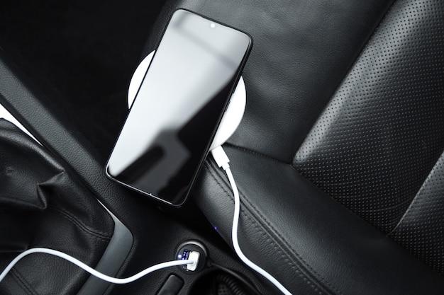 Telefone celular, bateria de carga do smartphone, carregamento sem fio no plugue do carro