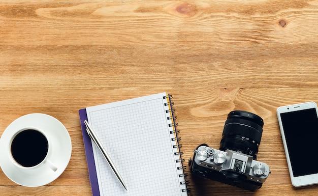 Telefone celular, caneta e bloco de notas, caneca de café e câmera em uma mesa de madeira