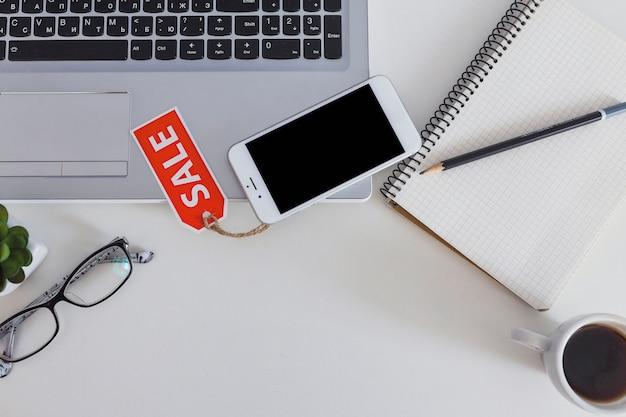 Telefone celular com etiqueta de venda sobre o teclado moderno laptop