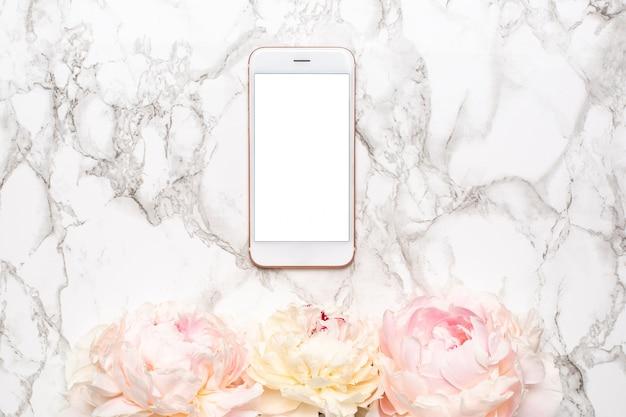 Telefone celular com flores piony brancas e rosa em uma superfície de mármore