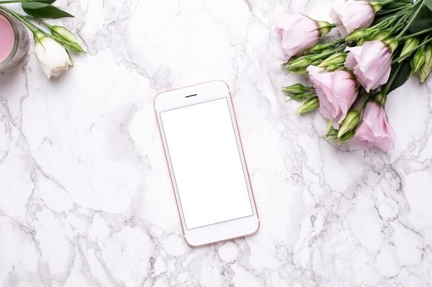 Telefone celular com flores rosa em mármore