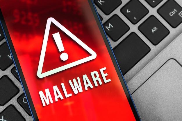 Telefone celular com sinal de malware na tela, plano de fundo do laptop, spyware e foto do conceito de sistema de segurança