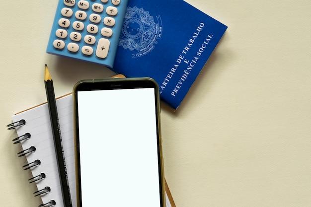Telefone celular com tela branca - cartão de trabalho brasileiro e calculadora conceito de controle financeiro