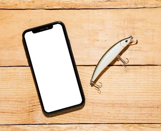 Telefone celular com tela branca e isca de pesca na mesa de madeira