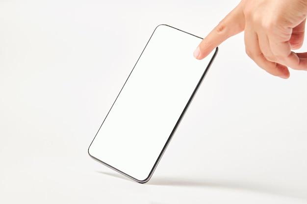 Telefone celular com tela em branco sobre fundo branco, com espaço de cópia. tela em branco da maquete do smartphone isolada com traçado de recorte