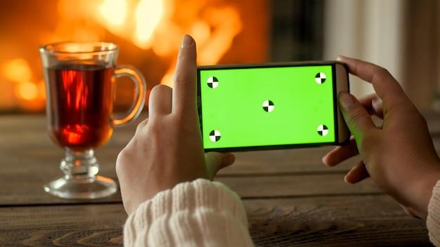 Telefone celular com tela verde contra lareira a lenha. lugar para o seu design