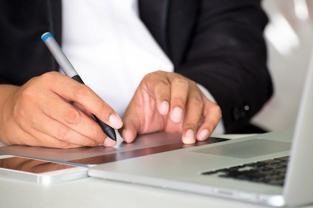 Telefone celular da tabuleta do caderno das informações da pesquisa do homem de negócios no escritório.