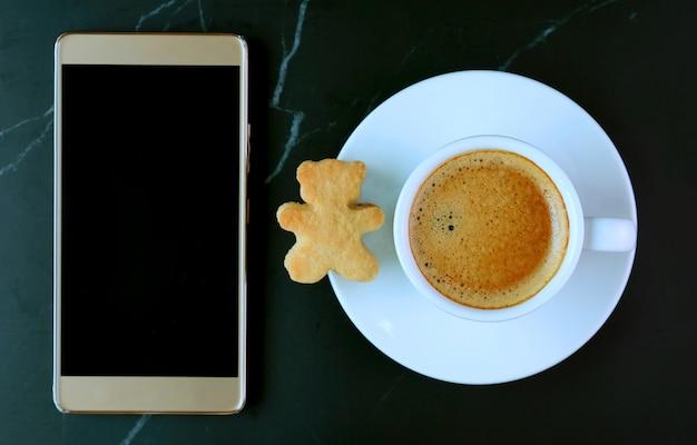 Telefone celular de tela vazia com uma xícara de café e biscoito em forma de urso de pelúcia na mesa de mármore preto