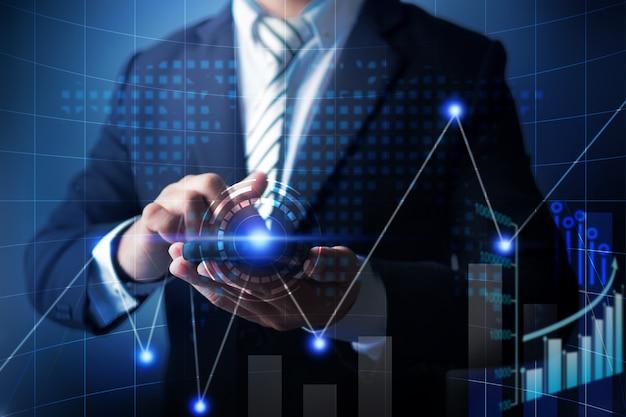 Telefone celular do uso do homem de negócios a analisar dados do negócio da finança com carta digital econômica do gráfico.