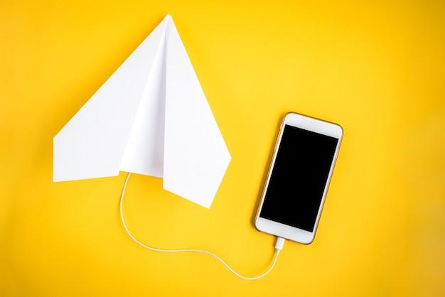 Telefone celular e avião de papel em amarelo