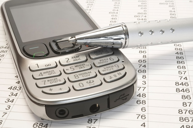 Telefone celular e caneta no papel