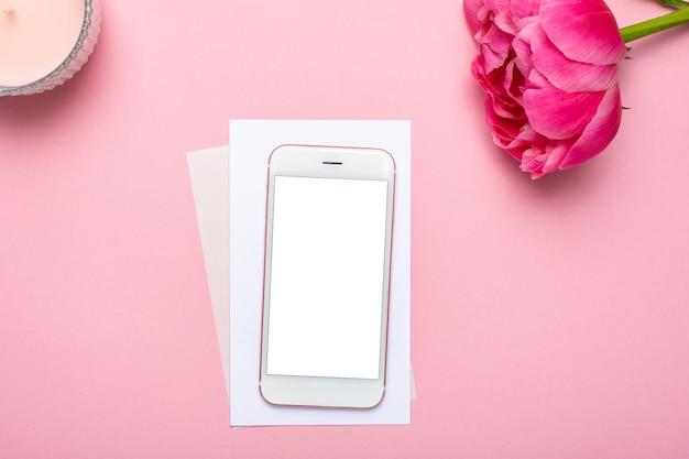 Telefone celular e flor de peônia na mesa-de-rosa pastel em estilo plano leigo. mesa de trabalho feminino. cor de verão