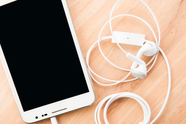 Telefone celular e fones de ouvido na parede de madeira com espaço.