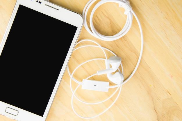 Telefone celular e fones de ouvido no fundo de madeira com espaço.