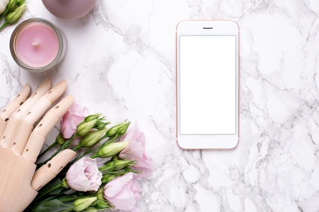 Telefone celular e mão de madeira com flores rosa em mármore