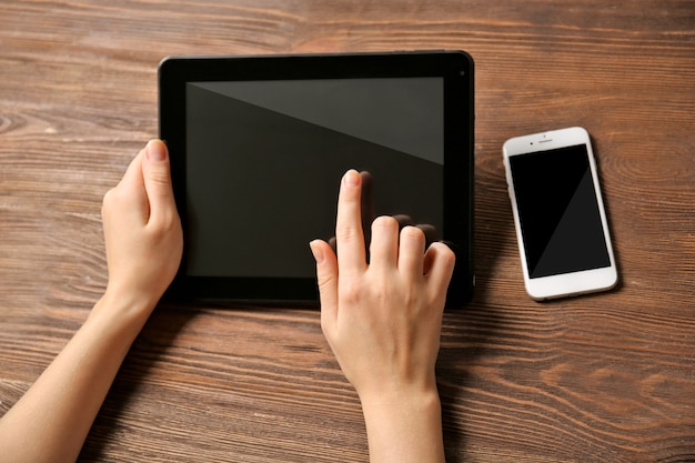 Telefone celular e mãos femininas usando tablet, no fundo de madeira