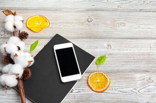 Telefone celular e ramo algodão flor em cima da mesa. vista do topo.