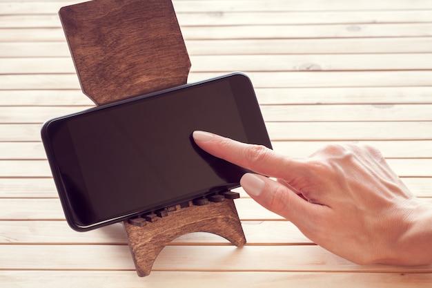 Telefone celular e uma mão feminina