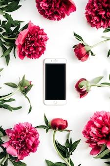 Telefone celular em uma moldura de flores de peônias rosa na superfície branca