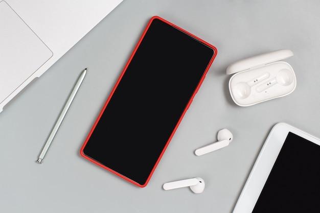 Telefone celular, fones de ouvido e tablet vermelhos perto do laptop em fundo branco