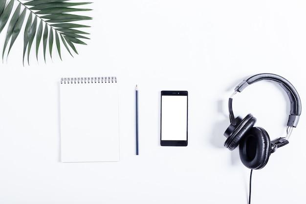 Telefone celular, fones de ouvido pretos, caderno, lápis e folhas verdes deite-se sobre uma mesa branca