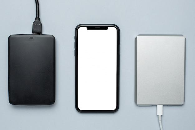 Telefone celular mock up e discos rígidos removíveis em cinza