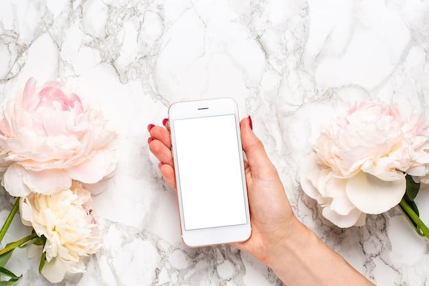 Telefone celular na mão com flores piony brancas e rosa em uma superfície de mármore