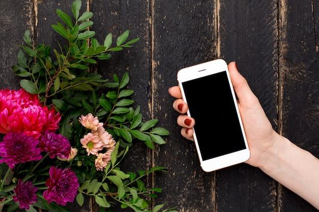 Telefone celular na mão feminina e um buquê de flores em uma madeira preta