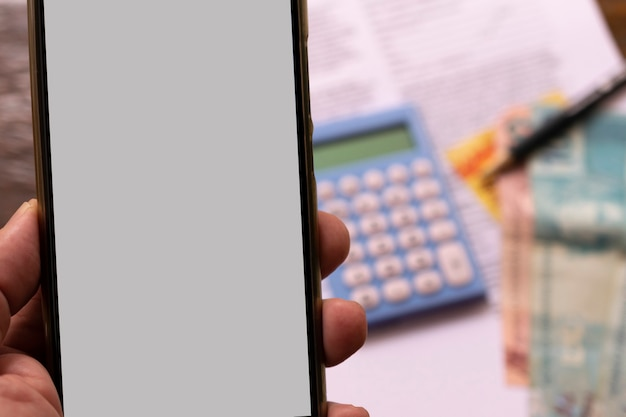 Telefone celular nas mãos com tela branca. fundo desfocado com dinheiro, calculadora e lápis