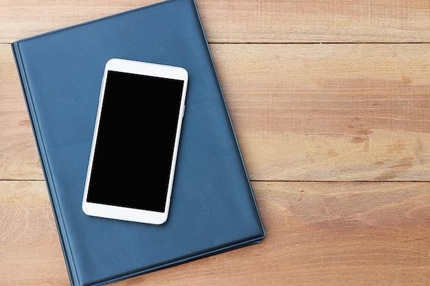 Telefone celular ou smartphone e livro na mesa de madeira.