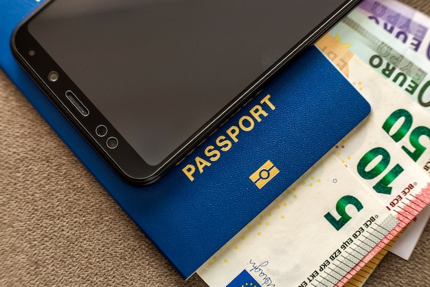 Telefone celular preto moderno, notas de cédulas de dinheiro euro e passaporte de viagem. luz de viagem, conceito de viagem confortável.