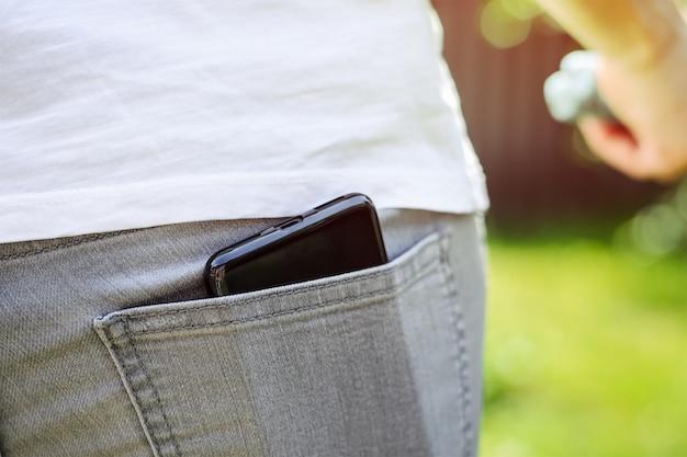 Telefone celular preto no bolso de trás de jeans cinza