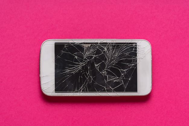 Telefone celular quebrado com exposição rachada no fundo roxo.