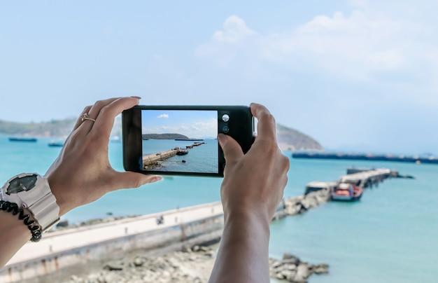 Telefone celular smartphone, tirando fotos de mar e vista para a montanha