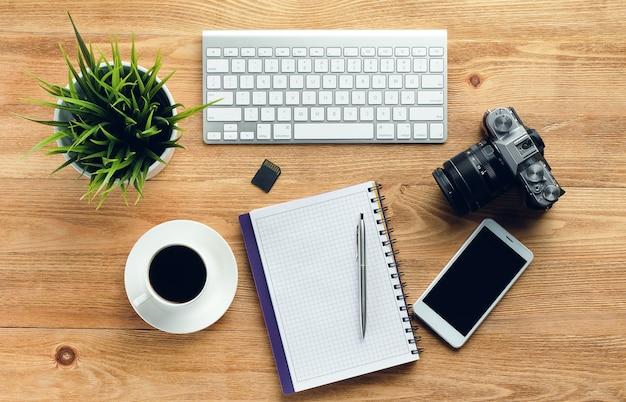 Telefone celular, teclado de computador, caneta e bloco de notas, caneca de café, pen drives e câmera em uma mesa de madeira