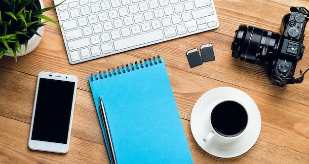 Telefone celular, teclado de computador, caneta e bloco de notas para anotações, caneca de café, unidades flash e câmera em uma mesa de madeira. itens do fotógrafo no local de trabalho.