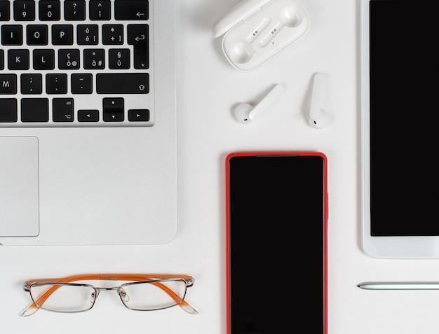 Telefone celular vermelho, fones de ouvido e óculos perto do laptop em fundo branco