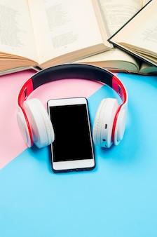 Telefone com fones de ouvido e livros abertos sobre fundo de papel colorido.