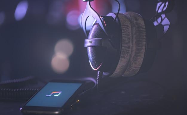 Telefone com ícone da música e fones de ouvido no fundo desfocado, conceito de escuta de música, espaço de cópia.